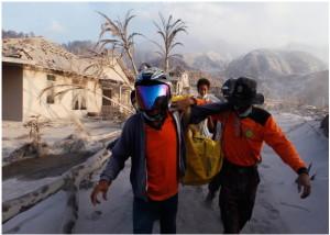 Para relawan membawa korban letusan gunung Merapi di Desa Kinahrejo, kabupaten Sleman pada tanggal 27  Oktober 2010.